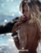 dame op het strand met vingers voor de mond met bote schouder met zand erop en mooie blonde zonverlichte haren ter illustratie van de medavita solarich zonneproducten voor haar en huid.