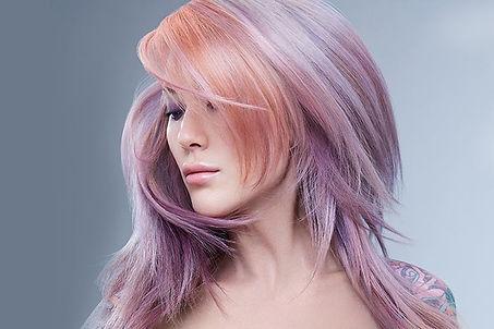 dame met pastelkleurige haren geverfd met de professionele haarkleuren van Aloxxi.