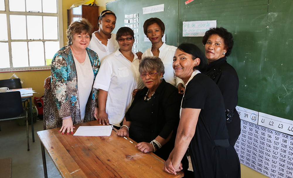 MathMoms and Mentor with the MD at Uitsig Primary School. From left to right. Standing: Sonja Cilliers, Magdalene Williams, Hilary Thai, Danielle Charles and Lily Cornelius. Seated: Jenni Fortuin (MathMentor) and Mavis Crayvenstein