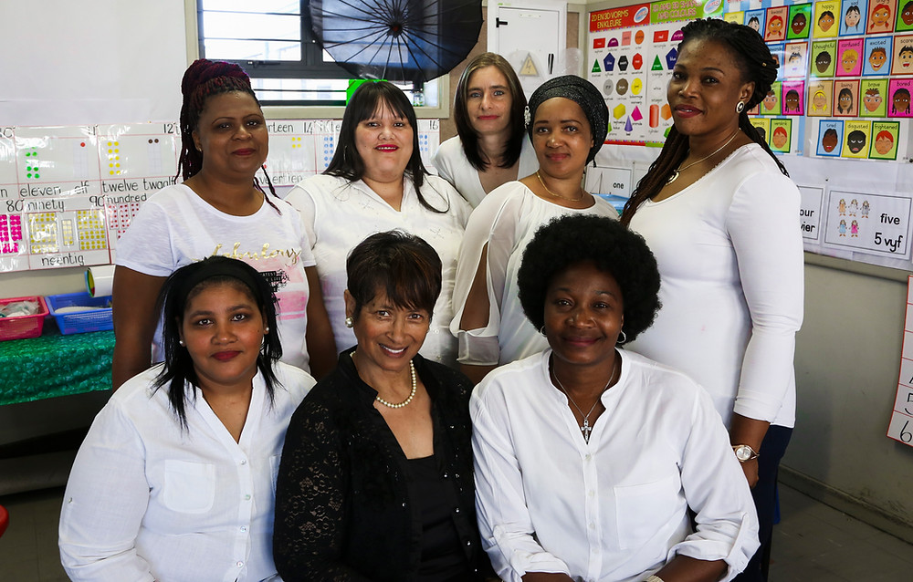 MathMoms (in white) with the Mentor and Director at Valhalla Primary. From left to right. Standing: Susanne Blou, Chevonne Groenemeyer (both completed ECD Courses at Northlink College at the end of 2020), Marlene Batt (found permanent employment), Maria Amram and Laurance Mtambo. Seated: Denise Sauls (MomMentor), Bertha Losper (MathMentor and Director) and Nene Omena