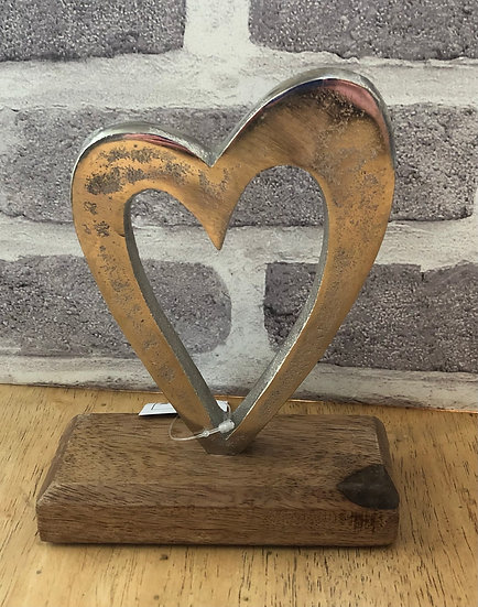 Metal heart on wooden base.