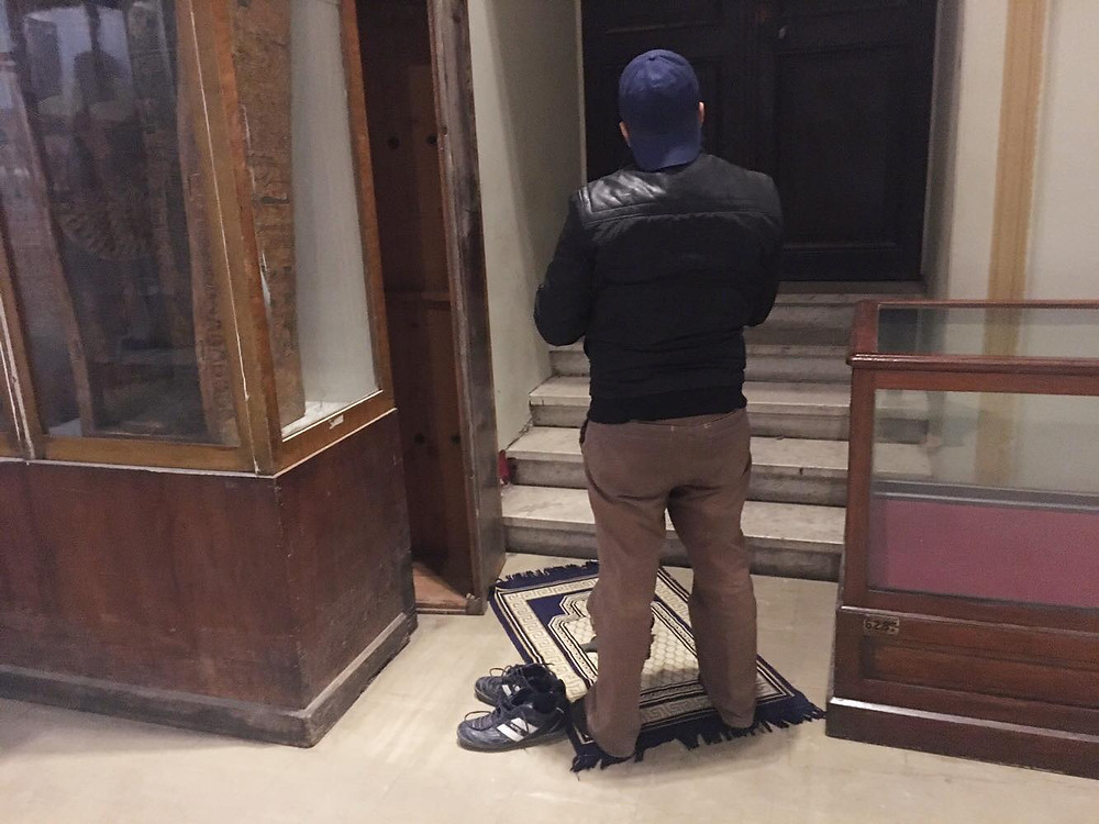 someone stops and prays in the Egyptian Museum.