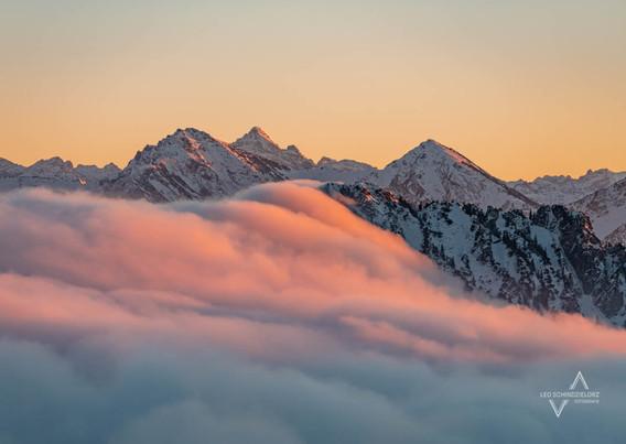Romantischer Blick auf das Gipfelkreuz des Sorgschrofen und dem Hochvogel im Hintergrund
