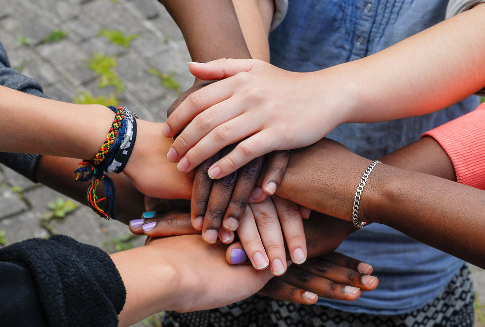 Multiracial teenagers joining hands toge