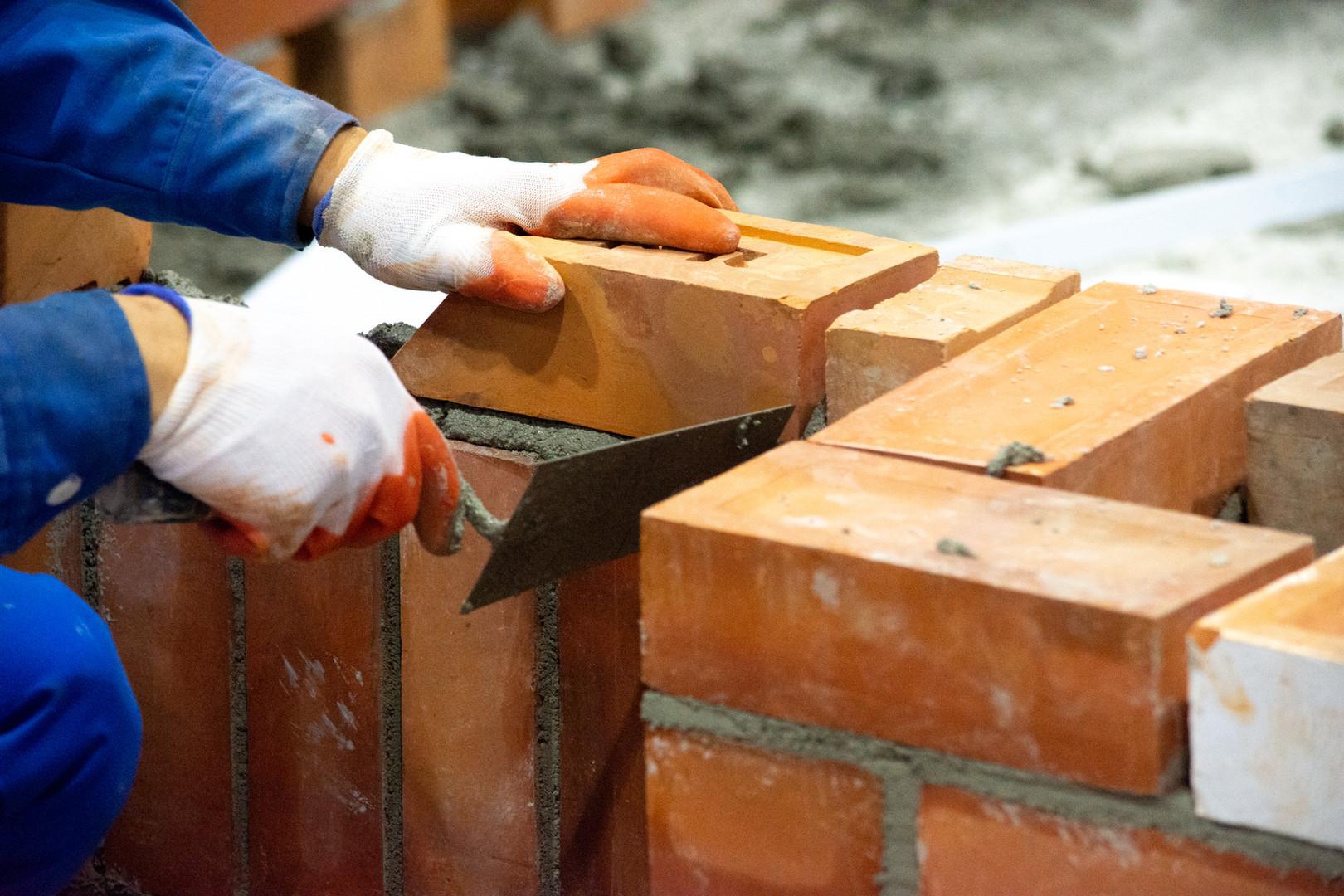 Bricklayer installing bricks, Bricklayer