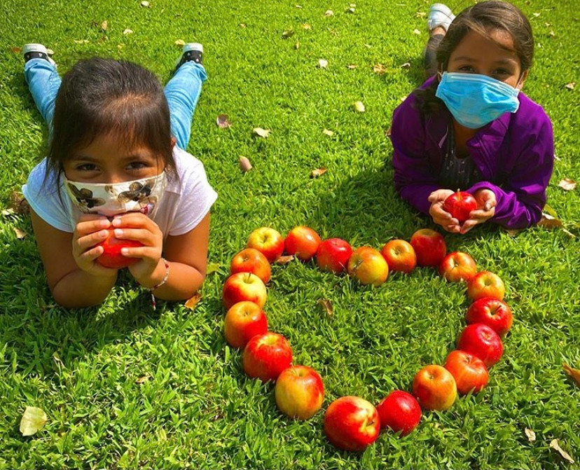 Two NVCS students sitting on the grass with apples