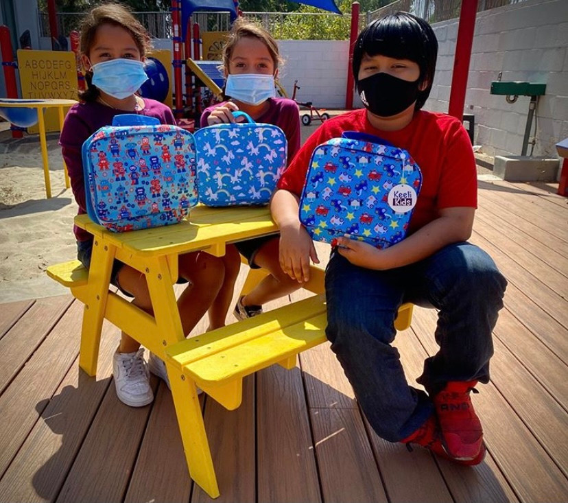 NVCS students sitting at a yellow lunch table holding lunch bags