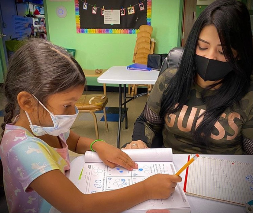 NVCS student doing classwork with a volunteer