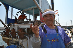 arahama sato fisherman on boat holds shell catch.JPG