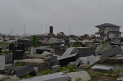 arahama debris gravestones piled, houses hanging in wind 2011.JPG