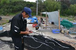 naburi yamato fisherman mends net on beach lean two .JPG