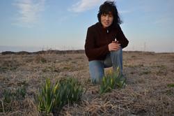 minamisoma tamura looks at camera daffodils on land.JPG