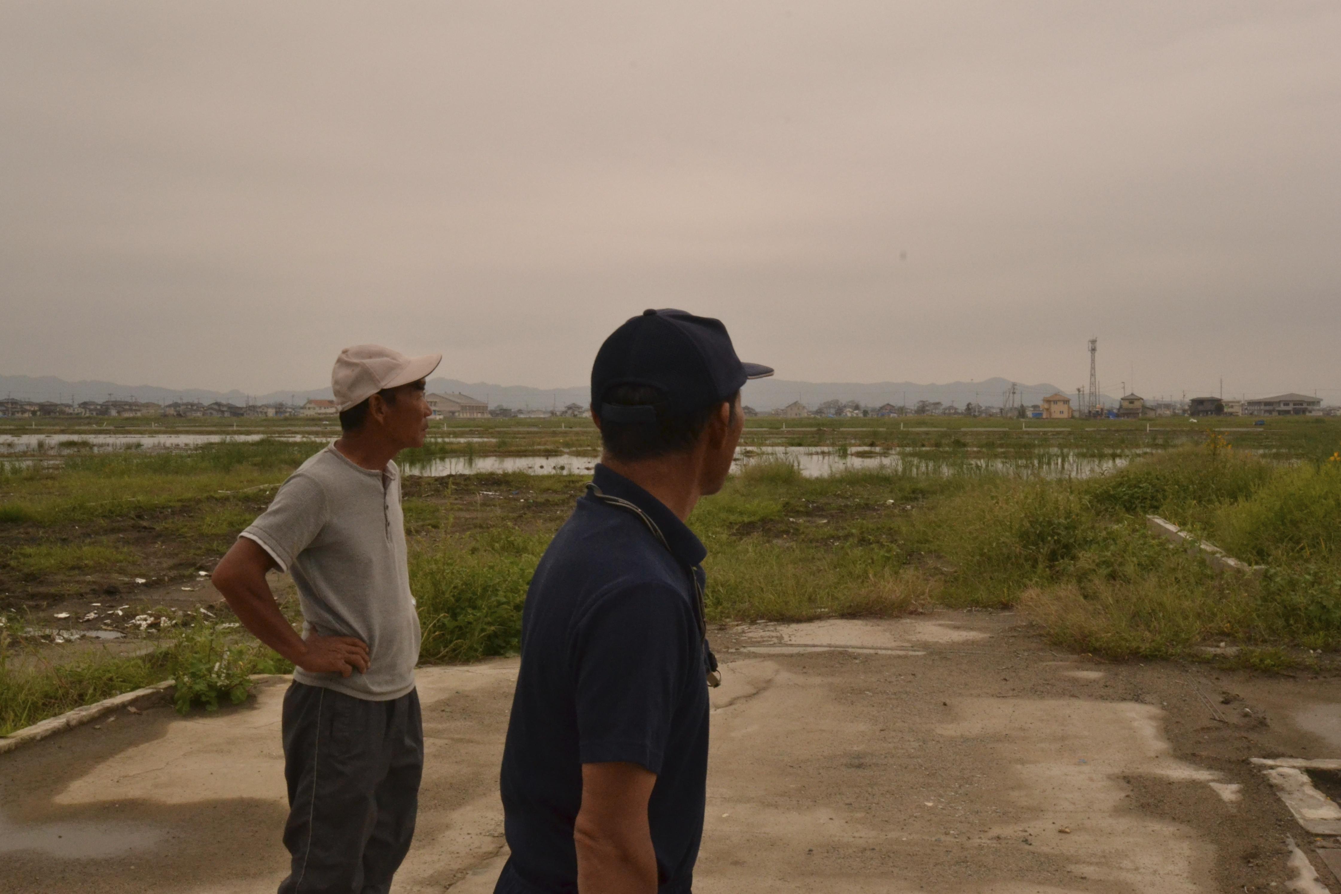 watari fishermen mori brothers look at their crumbled homes.jpg