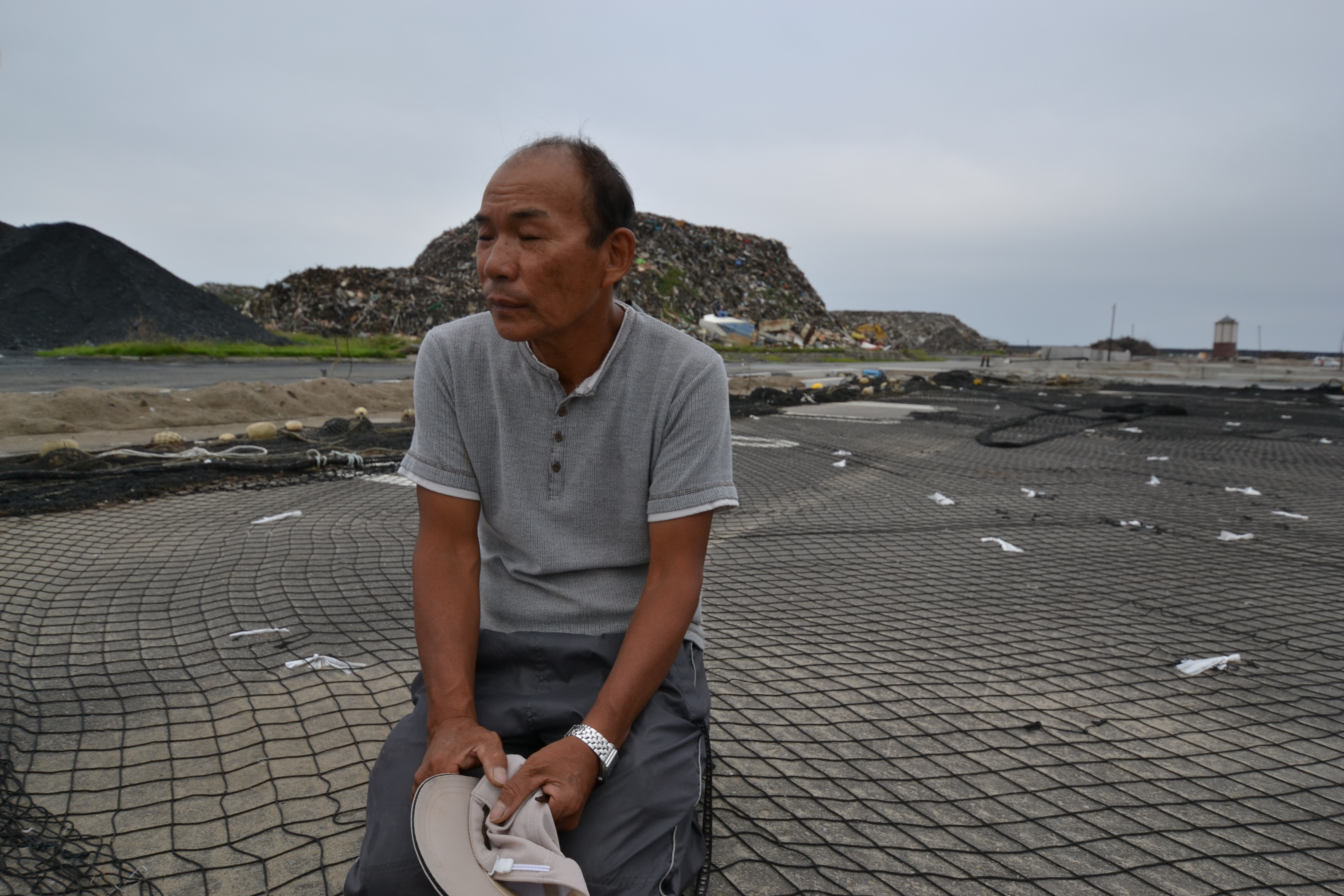 watari mori fisherman on knees eyes closed on broken nets.JPG
