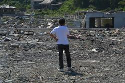 onagawa lone man stands in debris looks at house.JPG