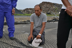 watari fisherman mori on knees with broken nets, broken heart mountain debris.JPG