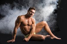 Attractive shirtless muscular man sittin
