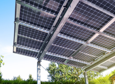 How can parking lots be transformed into income-producing solar carports?
