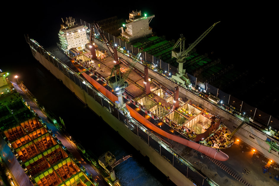 Aerial view container ship and oil in shipyard for repair at night. Can use for shipping o