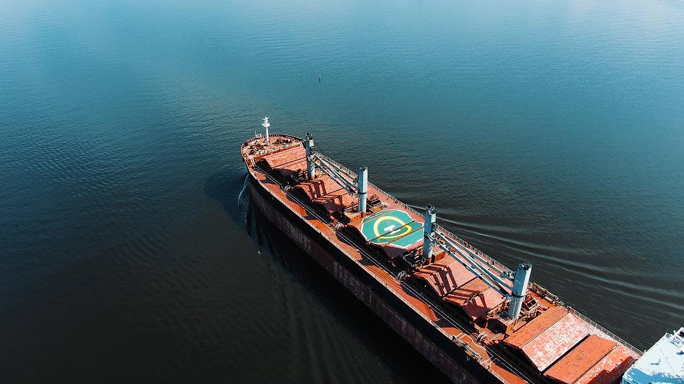 pictorial brown cargo ship sails on endless blue ocean.jpg