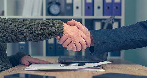 man-and-woman-shaking-hands-over-busines