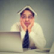 Homme songeur assis devant son ordinateur avec un livre sur la tête.