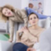Mère contrariée avec enfant un hyperactif sautant sur le fauteuil.