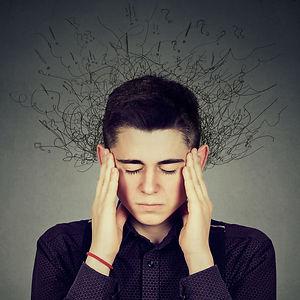 Jeune adolescent perturbé se tenant les tempes avec ses mains.