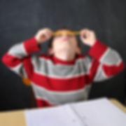 Jeune garçon tentant de faire tenir un crayon en équilibre sur son nez.