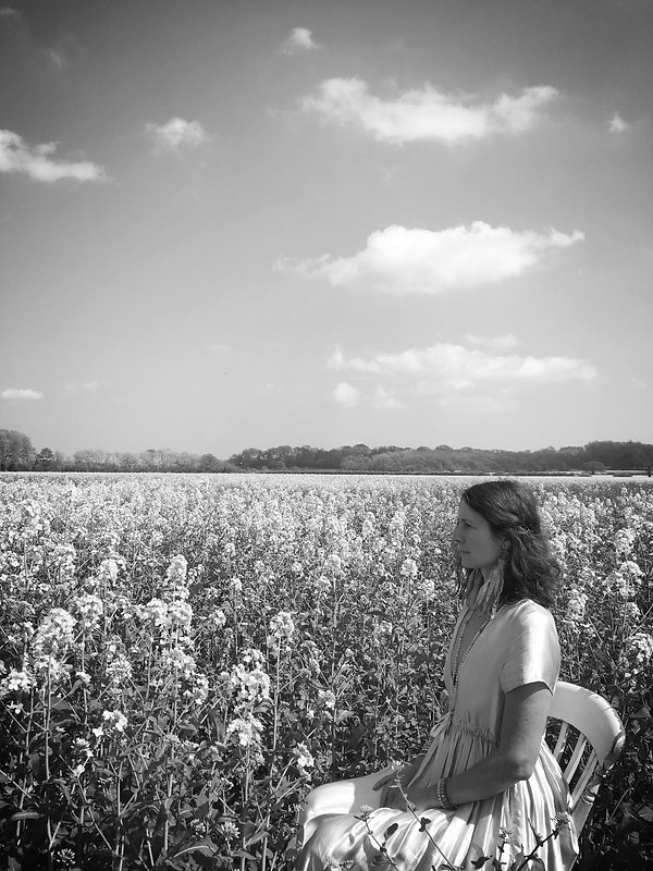 sitting on a chair in a field of flowers