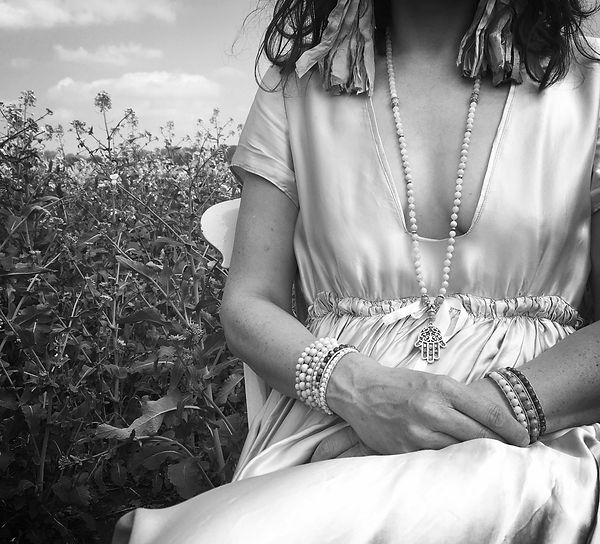 woman with jewellery and dress sitting in a field