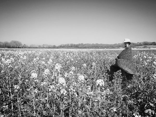 woman in a field of flowers with hat and kantha blanket