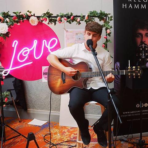 Keegan Hammond singing with Neon backdrop