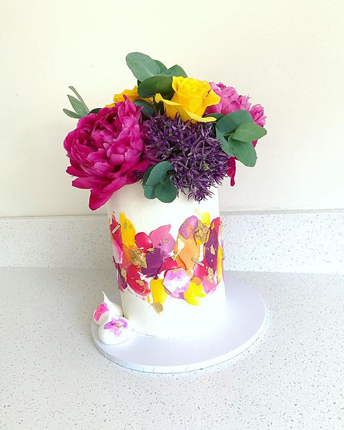 brightly coloured cake with real flowers