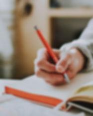 person-holding-orange-pen-1925536.jpg