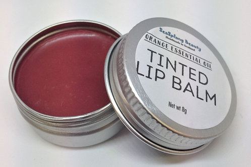 Opened labelled aluminium tin with dark red lip balm