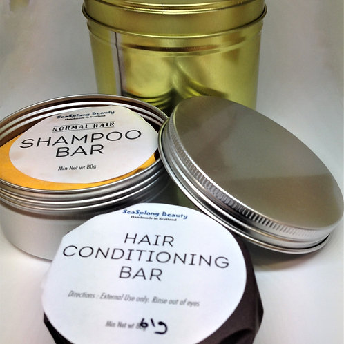 A gold  and a silver open tin showing the wrapped shampoo and conditioning bars