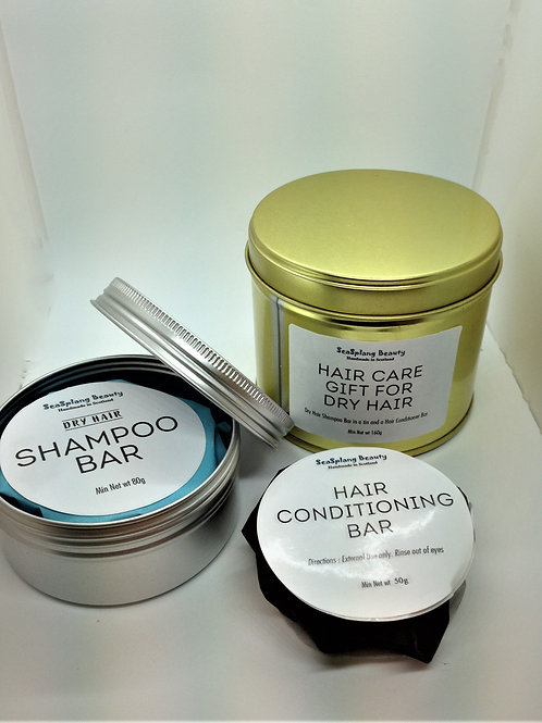 A gold and opened silver tin with the wrapped shampoo bar and hair conditioning bar