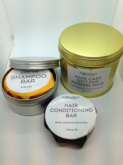 A gold and an opened silver tin with a wrapped shampoo bar and a hair conditioning bar