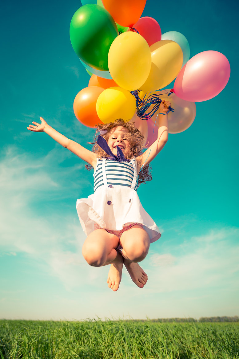 Happy child jumping with colorful toy ba