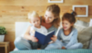 happy family mother reading to   childre