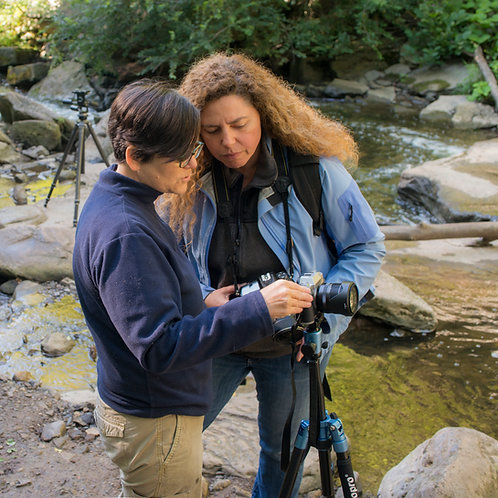teacher giving camera lessons to photo student, waterfall landscape