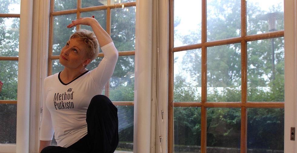 Method Putkisto Pop Up Studio Jyväskylä harjoittelet mukavassa seurassa ja omaa kehoasi kuunnellen kohti elämän kestävää ryhtiä ja parempaa oloa. Kuvassa ohjaaja Maikku Tyrväinen näyttää sivukurkea / hartiavenytys.