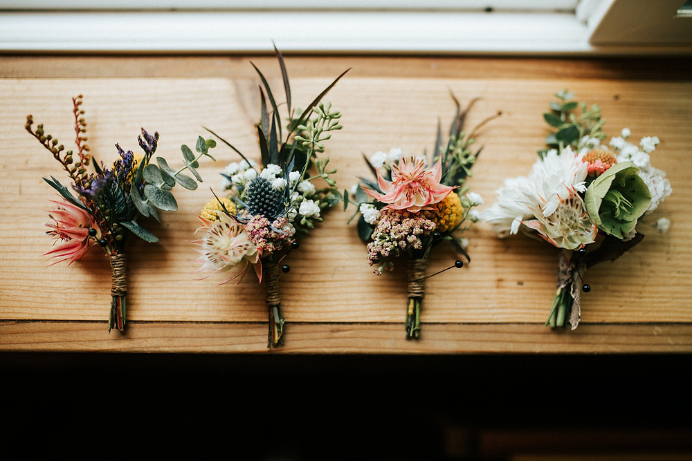 Floral boutonnieres on a wood window sill
