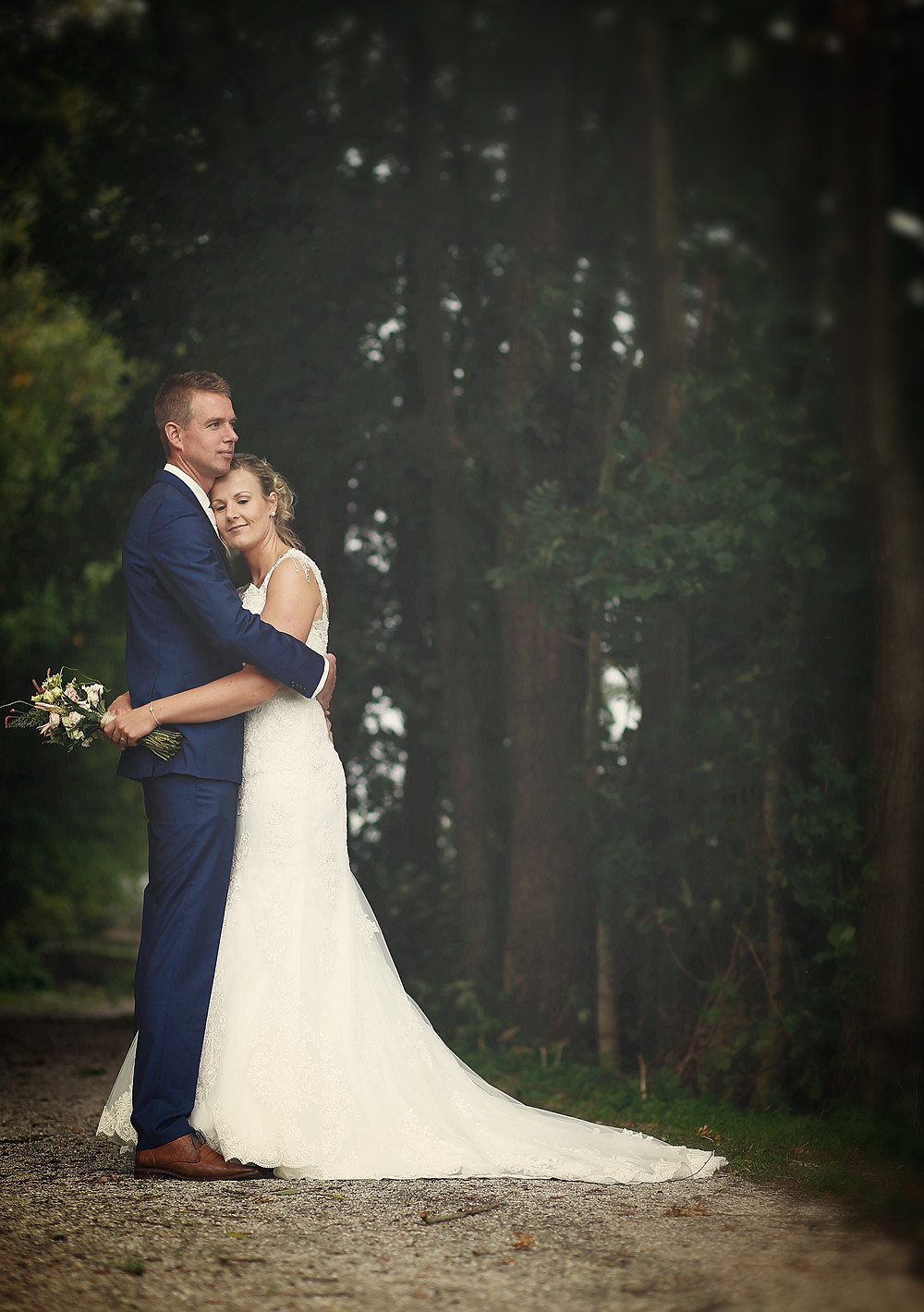 Wedding day couple hugging in the woods