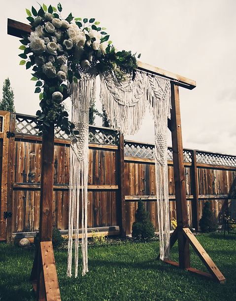 Wooden arbour, with floral arrangement and macrame hanging