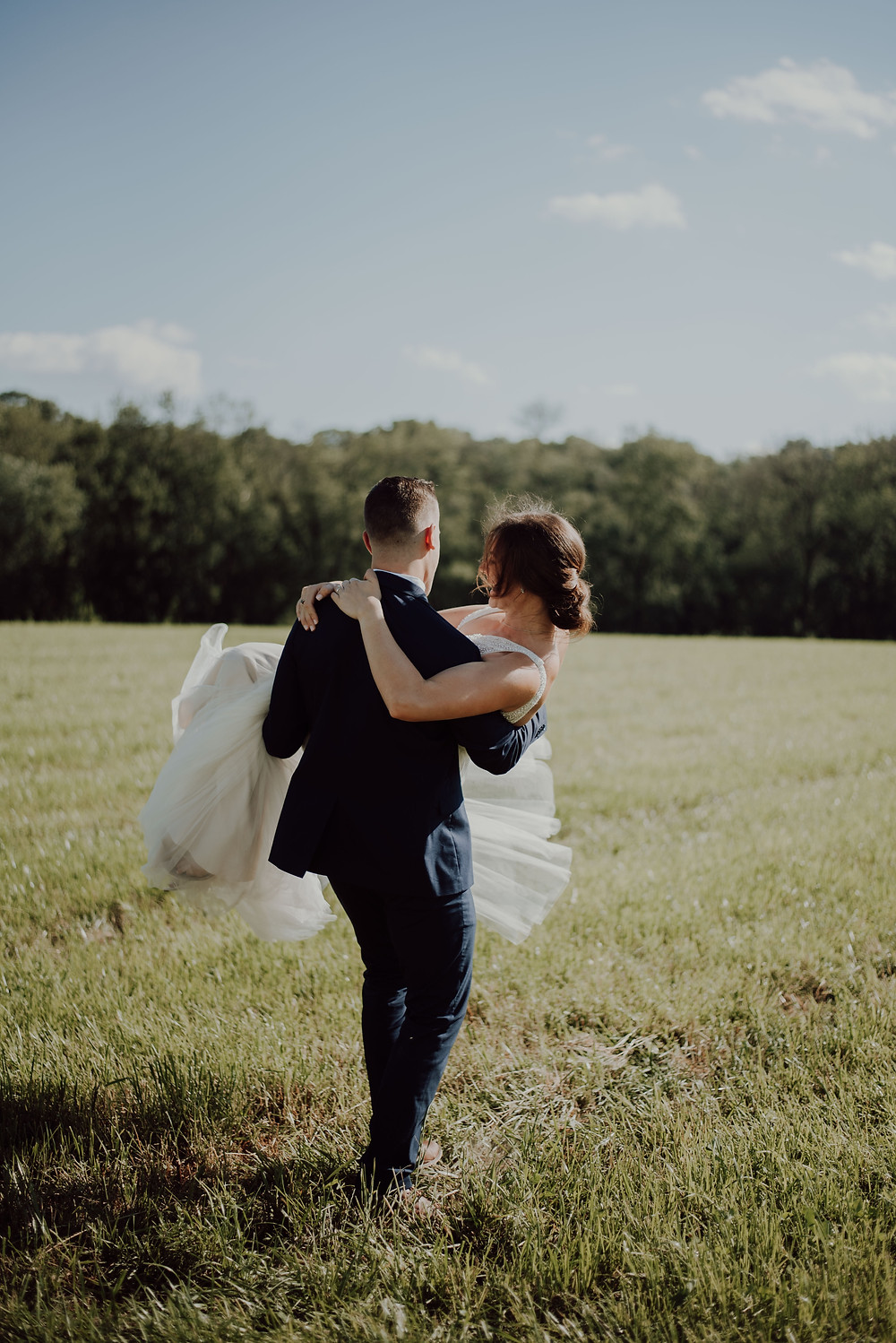 Groom carrying bride through a grassy field
