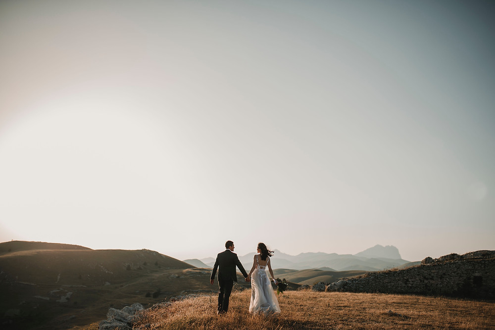 Couple holding hands on a vast field overlooking mountains