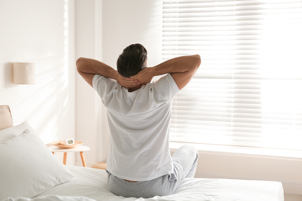 Man in bed, stretching in the morning light.