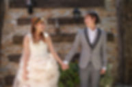 Young newlywed couple holding hands after wedding in rustic background